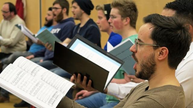 Ein Chor bei der Probe: Männer mit einem Notenblatt in der Hand singen.
