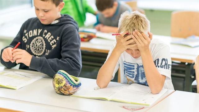 Ein Schuljunge stützt den Kopf in die Hände.