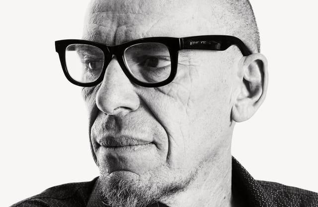 Schriiftsteller Tom Kummer mit dunkler Brille, ernst schauend.