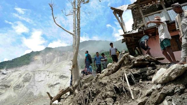 Menschen neben einem zerstörten Haus schauen auf den abgerutschten Berghang.