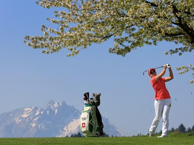 Die Golferin Fabienne In-Albon beim Golfspielen - im Hintergrund der Pilatus.