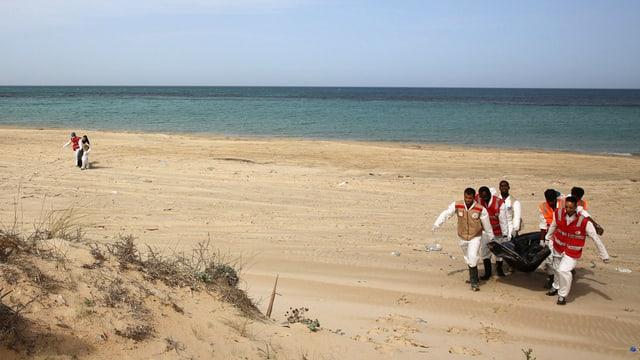 Mitarbeiter vom Roten Kreuz bergen eine Leiche an der libyschen Mittelmeerküste.