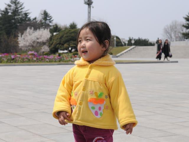 Kleines Kind in gelber Jacke.