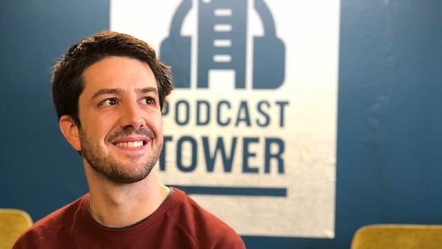 Ein Mann mit Dreitagebart und kurzen braunen Haaren sitzt vor einer Wand mit der grossen Aufschrift: Podcast Tower.