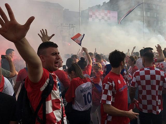 Jubelnde Fans und Rauchschwaden.