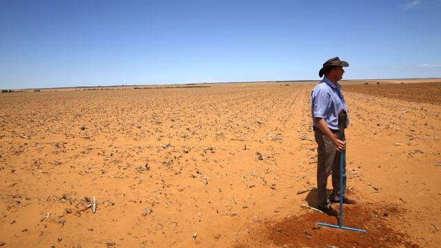 Ein weisser Farmer steht einsam auf einem riesigen, braunen Feld.