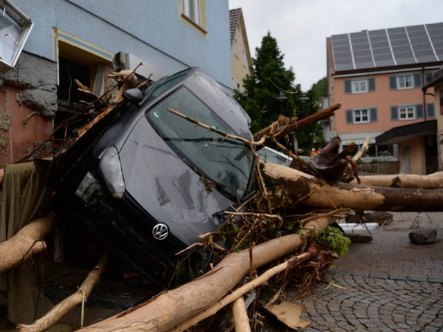 Ein von den Wassermassen mitgerissenes Auto liegt in Schräglage auf Baumstämmen.