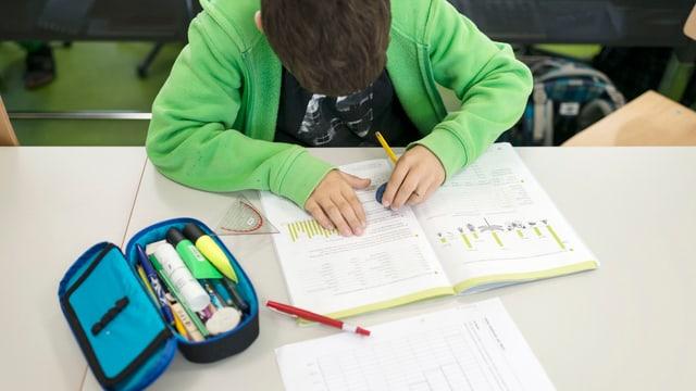 Schüler arbeitet in einem Schulheft