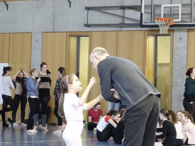 Ein Mann spricht mit einem kleinen Mädchen während einer Orchesterprobe