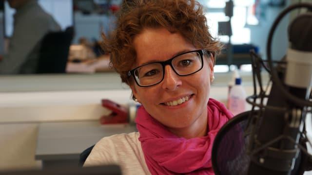 Nadja Räss mit rosa Schal, sitzend im Studio hinter einem Mikrofon.