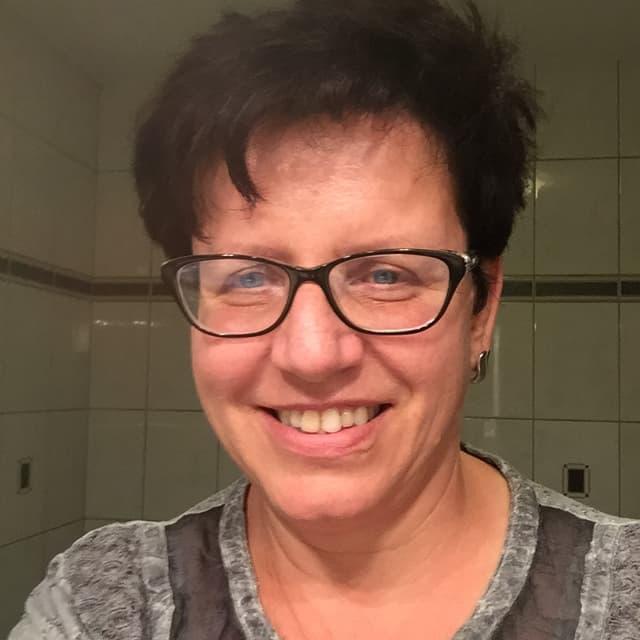 Frau mit dunklen Haaren und dunkler Brille.