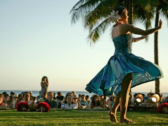 Eine Hula-Tänzerin auf Hawaii, bebobachtet von einem grossen Publikum.
