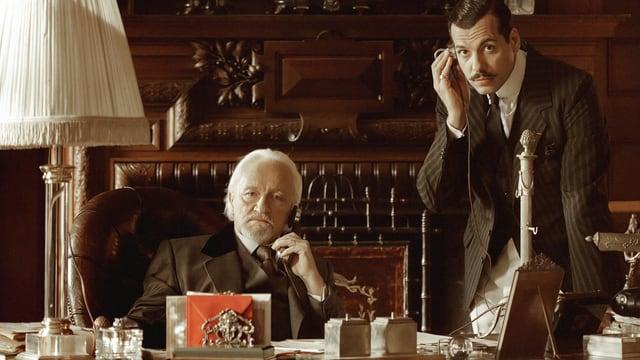Zwei Männer an einem Bürotisch.