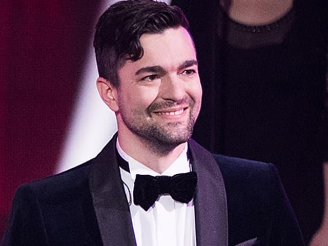 Samuel steht auf der ESC-Bühne und lächelt