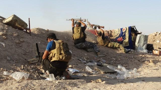 Kämpfer schiessen mit Gewehren hinter einem Sandwall