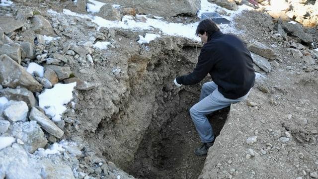 Ein Mann in einem 1.5 Meter tiefen Erdloch.