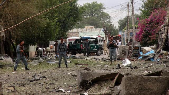 Drei bewaffnete Sicherheitskräfte vor den zerstörten Gebäuden.