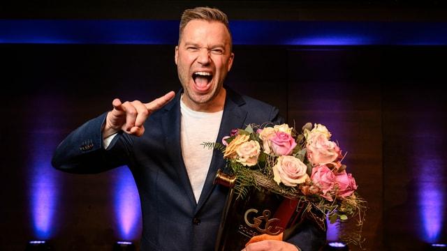 Mann mit Grimasse und Blumenstrauss in der linken Hand