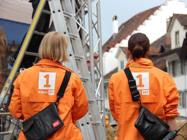 Zwei Mitarbeiterinnen schauen den Aufbauarbeiten zu.