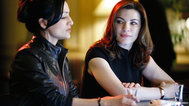 Zwei Frauen diskutieren an einer Bar.
