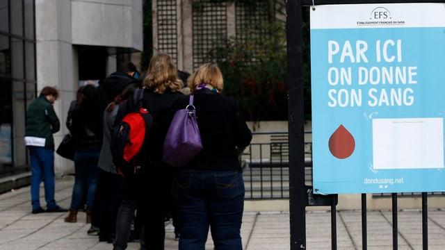 Menschen stehen Schlange vor einem Blutspendezentrum mit einem blauen Schild davor.