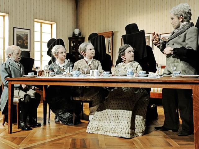Als alte Menschen maskierte Kinder sitzen um einen Tisch, im Hintergrund schwarze Gestalten.