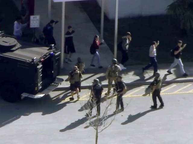 Schüler verlassen die Schule mit erhobenen Händen, Sicherheitskräfte stehen daneben