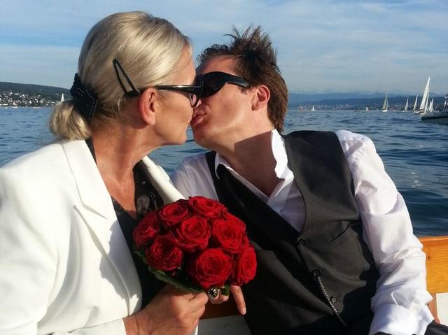 Sibylla und Pascal Ulli auf dem Schiff auf dem See, sie hält einen Strauss roter Rosen in der Hand und küsst ihren Mann.