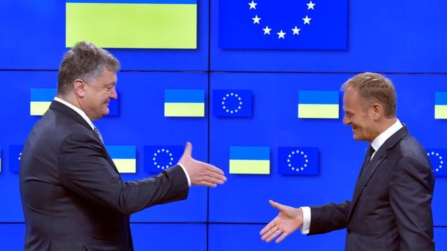 Tusk reicht dem ukrainischen Präsidenten die Hand.