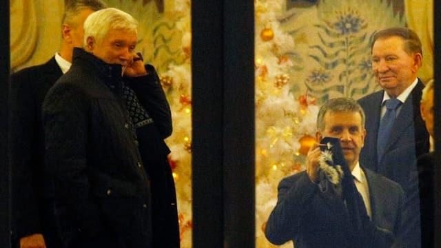 Russische Botschafter und Leonid Kutschma stehen hinter einem Fenster.
