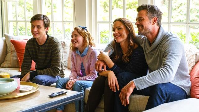 Eine Familie sitzt lachend vor dem Fernseher und schaut fern.