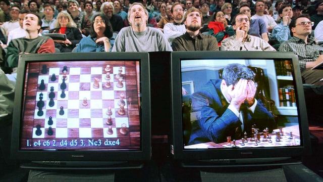 Auf zwei Monitoren sieht man den Schachcomputer und Kasparow vor einer sitzenden Menschenmenge.