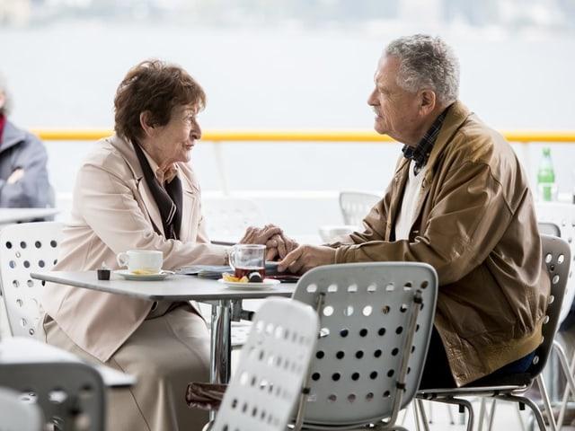 Eine Frau und ein Mann sitzen am Tisch.