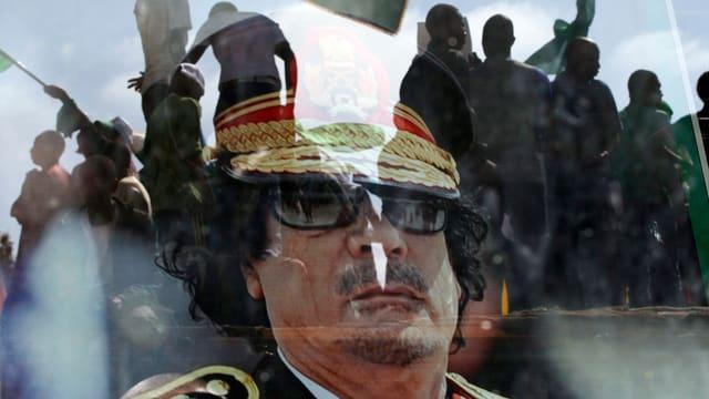 Der gestürzte Diktator Gaddafi, im Hintergrund Flüchtlinge.