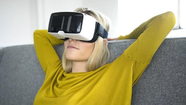 Eine Frau sitzt auf dem Sofa und trägt eine VR-Brille.