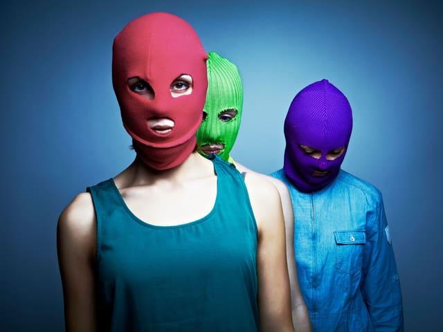 Drei Frauen mit farbigen Mützen über dem Gesicht.