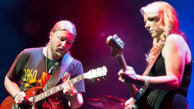 Der Gitarrist Derek Truck performt an der Seite einer blonden Frau.