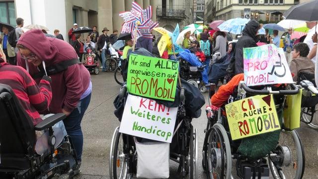"""Viele Rollstühle, bunt geschmückt mit Plakaten, auf denen Sprüche stehen wie """"Ich bin auch mobil"""""""