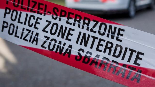 """Absperrband """"Polizei-Sperrzone"""", im Hintergrund sieht man in der Unschärfe ein Polizeiauto angedeutet."""