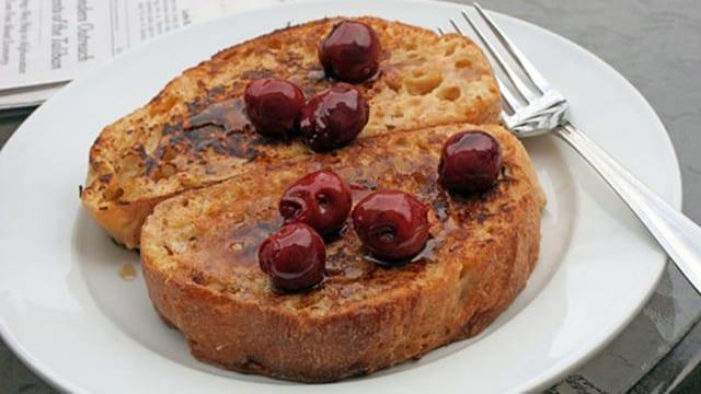 Zwei Scheiben Brot, mit Kirschen verziert, auf einem Teller.