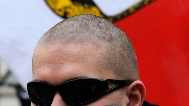 Skinhead vor NPD-Fahne