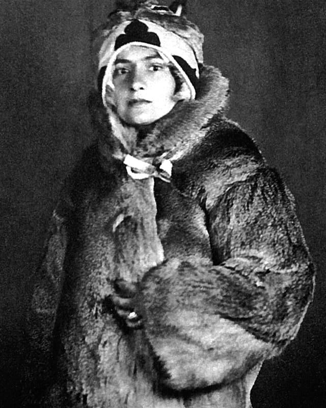 Altes Schwarzweissfoto: Eine junge Frau in einem dicken Pelzmantel.