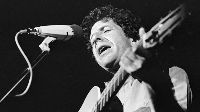 Der kanadische Musiker Leonard Cohen singt mit Gitarre in der Hand und geschlossenen Augen auf der Bühne des Jazz-Festivals in Montreux.