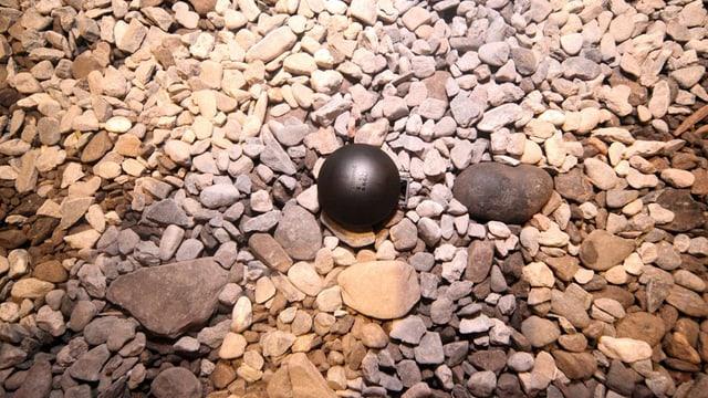 Eine schwarze Kugel, die Radon misst, auf einem Kiesboden