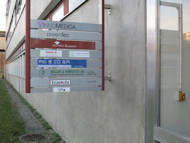 Ein Schild mit mehreren Firmennamen.