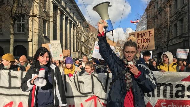 Eine Gruppe Schülerinnen läuft durch Zürich, vorneweg zwei junge Frauen mit einem Megafon in der Hand.