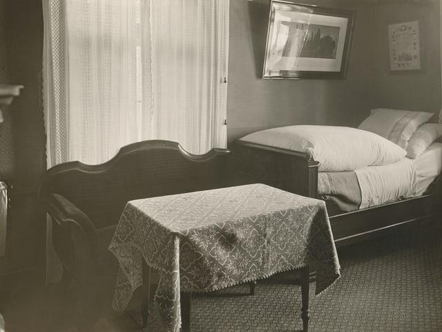 schwarz/weiss Bild von Zimmer mit Teppichboden kleinem Tisch und kleinem Bett