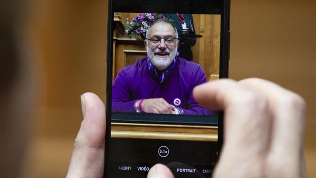 Ein Mann trägt ein lila Shirt.