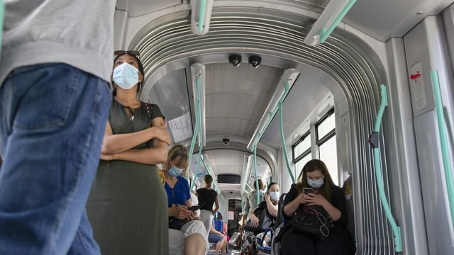 Purtret da persunas che portan mascras en il traffic public.