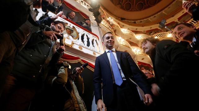 Luigi Di Maio wird von Presseleuten in einem Theatersaal umringt.